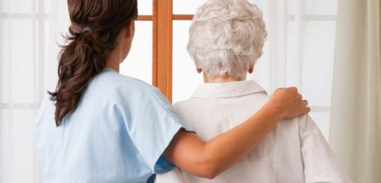 Nurse-helping-an-elderly-woman